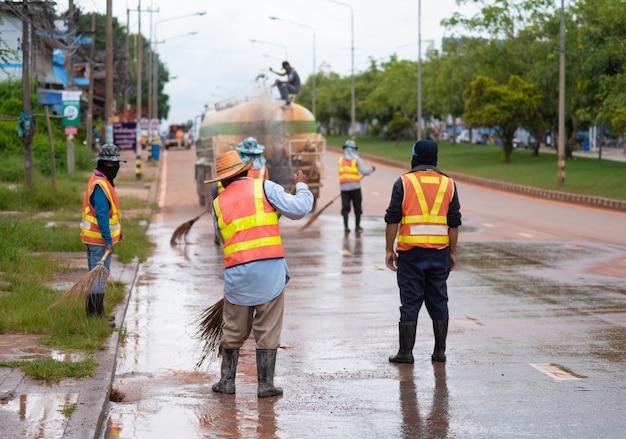 Straßenfegerarbeitskraft, die stadtstraße mit besenwerkzeug in thailand säubert
