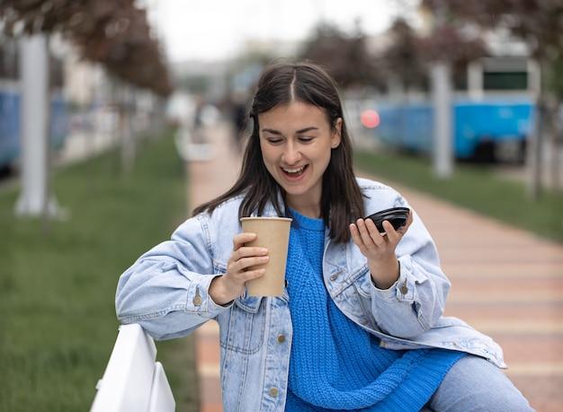 Straßenfoto einer attraktiven jungen frau, die mit einem kaffee in der hand auf einer bank sitzt.