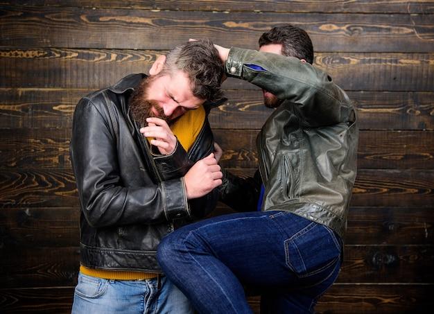 Straßenkampfkonzept. männer brutale hooligans tragen lederjacken kämpfen. physikalische attacke. männer bärtige hipster kämpfen. angriff und verteidigung. aggressiver hooligan, der mit einem starken tyrannen kämpft.