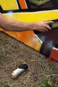 Straßenkünstler, der bunte graffiti an der wand malt.