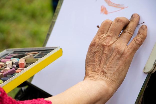 Straßenkünstler, der eine schachtel mit bunten buntstiften und bleistiften zum zeichnen hält. nahaufnahme von händen und zeichenzubehör. er zeichnet mit weißem papier hinter der staffelei.