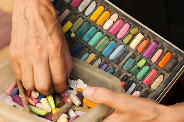 Straßenkünstler, der eine schachtel mit bunten buntstiften und bleistiften zum zeichnen hält