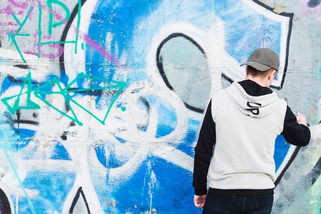 Straßenkünstler, der graffiti auf wand malt