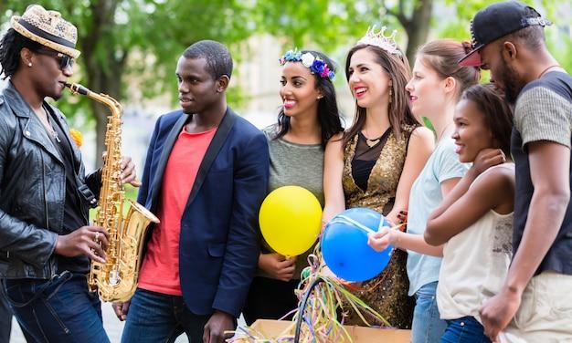 Straßenkünstler, der saxophon für multiethnische parteigruppe spielt