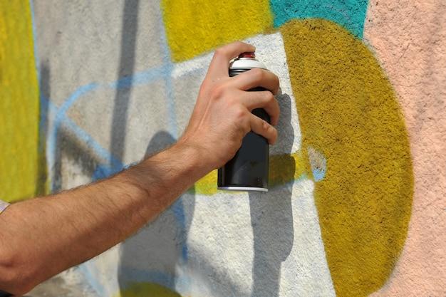 Straßenkünstler malt bunte graffiti an die betonwand. konzept der bunten modernen kunst.