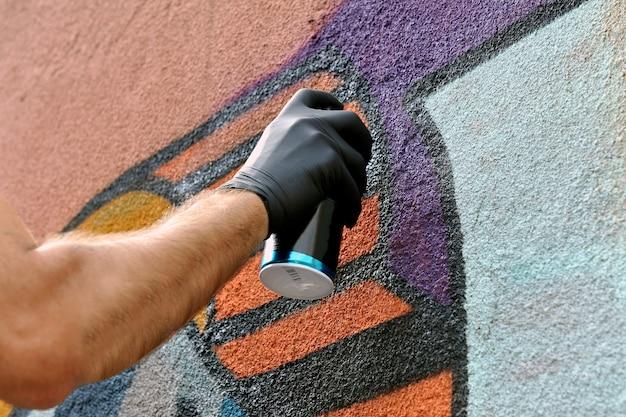 Straßenkünstler malt bunte graffiti an die betonwand.