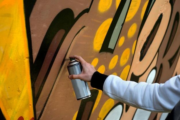 Straßenkünstler mit einem spray zeichnet bunte graffiti auf die betonwand