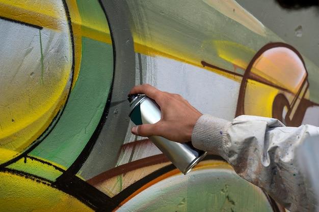 Straßenkünstler zeichnet bunte graffiti auf die betonwand.