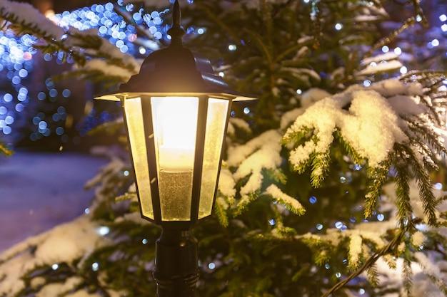 Straßenlampe. eingeschaltete straßenlaterne gegen geschmückten weihnachtsbaum und girlanden im schnee hautnah.
