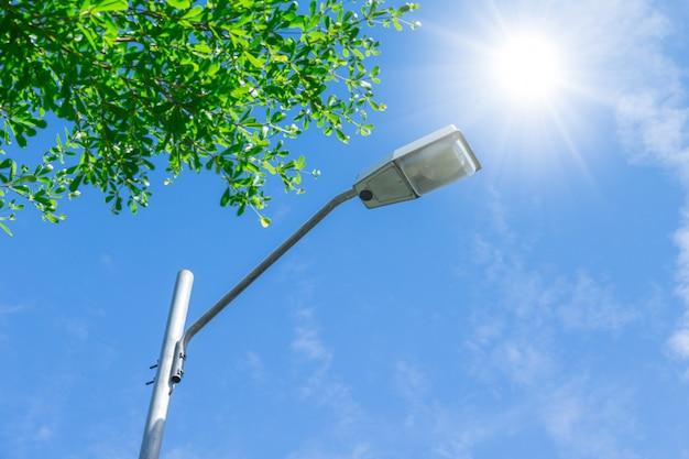 Straßenlampe im freien am sonniger tagesblauen himmel und am grünen baum