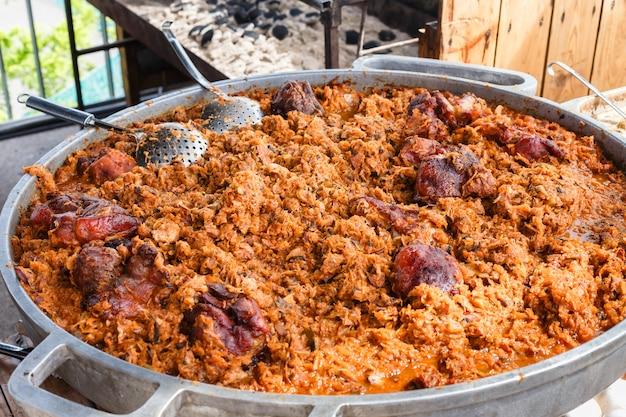 Straßenlebensmittel, schnellimbissfestival, köstlicher teller des gemüses, des kohls und des fleisches an der großen wanne in einem straßencafé