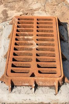 Straßenluke für die sturmkanalisation. nahansicht. straßenarbeiten. sammlung und entsorgung von regenwasser von der straße.