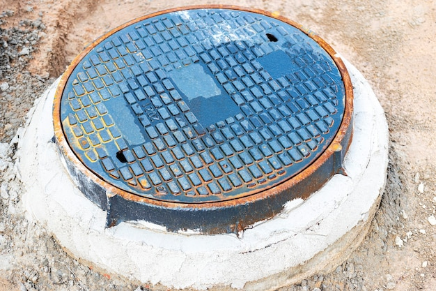 Straßenluke für wasserversorgung und kanalisation. nahaufnahme. straßenarbeiten. zugang zu unterirdischen versorgungsunternehmen.
