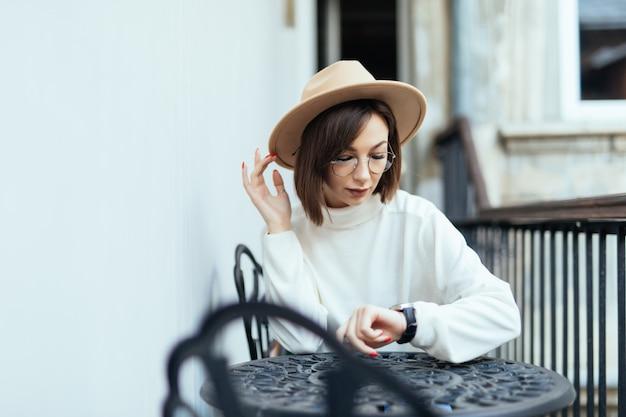 Straßenmodefrau mit moderner maniküre und transparenter brille, die am tisch sitzt