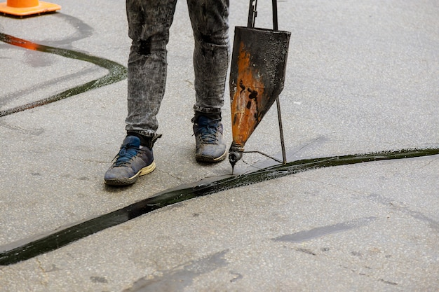 Straßenoberflächen-restaurierungsarbeiten im arbeiter führen bei straßenpflasterarbeiten die reparatur von rissen durch, indem die versiegelung mit einer mit bitumenemulsion beschichteten füllung gefüllt wird
