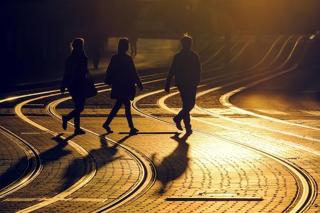Straßenphotographie von freunden machen einen spaziergang auf trameisenbahn während des sonnenuntergangs in der bordeauxstadt, frankreich.