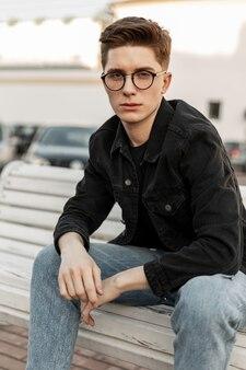 Straßenporträt amerikanischer junger mann mit vintage-brille in modischer denim-kleidung in der stadt bei sonnenuntergang. hübscher moderner typ in trendiger jeanskleidung sitzt draußen auf einer holzbank. lässige herrenmode.