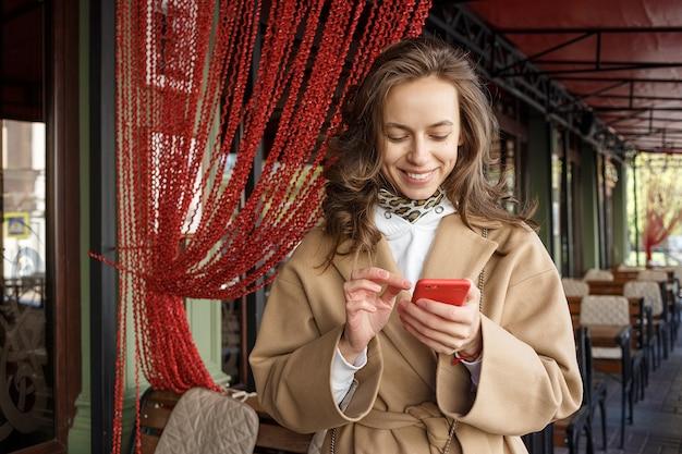 Straßenporträt der jungen lächelnden frau, die beige mantel unter verwendung ihres intelligenten telefons auf einer caféveranda trägt