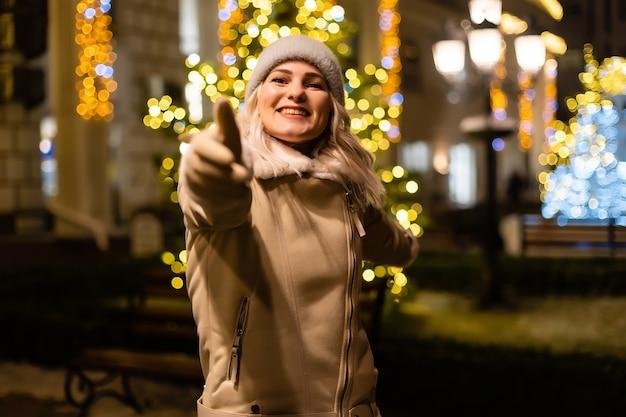 Straßenporträt der lächelnden schönen jungen frau auf dem festlichen weihnachtsmarkt. dame, die klassische, stilvolle winterstrickkleidung trägt.