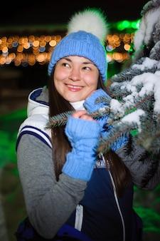 Straßenporträt der lächelnden schönen jungen frau auf dem festlichen weihnachtsmarkt