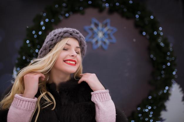 Straßenporträt der positiven jungen frau mit strickmütze und pelzmantel, die auf dem weihnachtsmarkt posiert. platz für text