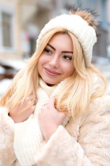 Straßenporträt einer entzückenden blonden frau mit weißem mantel und strickmütze, die im winter auf der straße posiert
