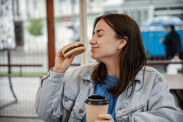 Straßenporträt einer fröhlichen jungen frau, die draußen einen burger und einen kaffee genießt.