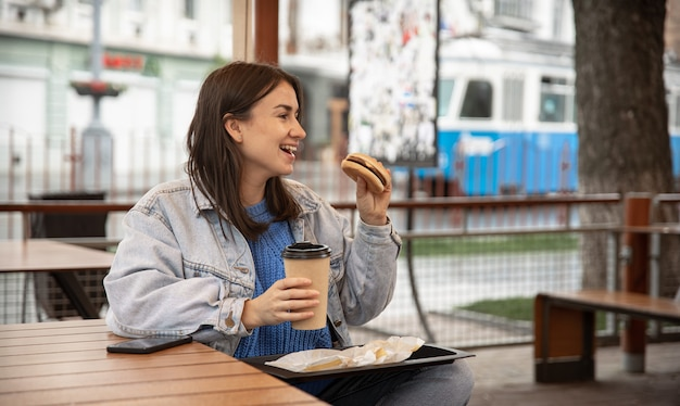 Straßenporträt einer fröhlichen jungen frau, die draußen einen burger und einen kaffee genießt
