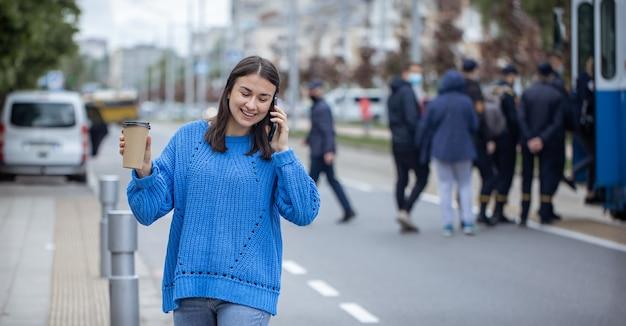Straßenporträt einer jungen frau, die in der stadt nahe der fahrbahn telefoniert