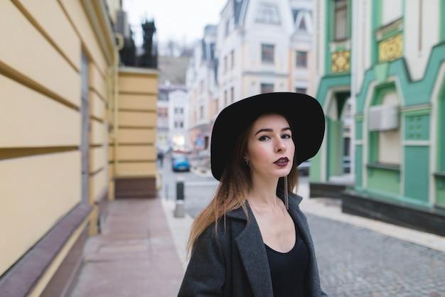 Straßenporträt einer stilvollen frau auf dem hintergrund der straße einer alten schönen stadt. Premium Fotos