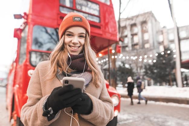 Straßenporträt einer süßen dame in hut und mantel, hört musik im kopfhörer, hält ein smartphone in den händen und schaut in die kamera