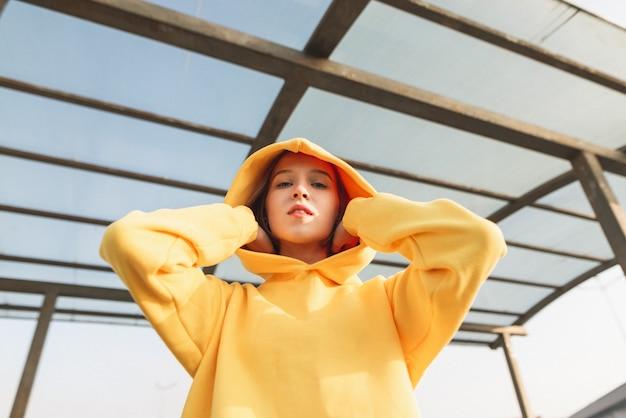 Straßenporträt eines stilvollen mädchens in einem gelben kapuzenpulli