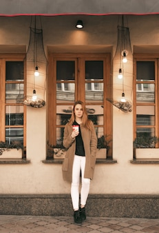 Straßenporträt eines stilvollen mädchens in vollem gange, das frühlingskleidung trägt, mit einer tasse kaffee in ihren händen steht und in die kamera schaut
