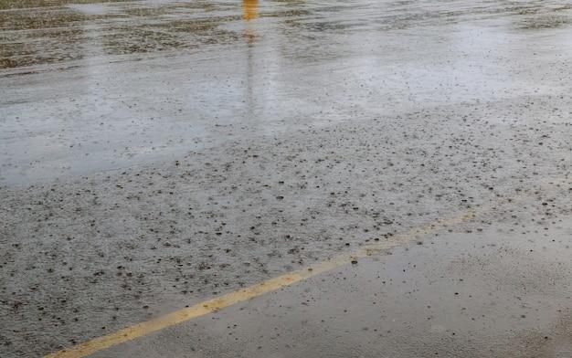 Straßenregenwasser lässt hintergrund mit reflexion des blauen himmels und kreise auf dunklem asphalt fallen. prognose.