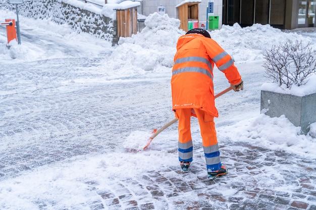 Straßenreinigungsarbeiter im leuchtend orangefarbenen mantel, der schnee von der straße an einer straße in st. moritz, schweiz aufräumt