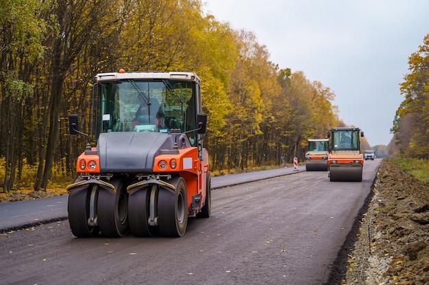 Straßenreparatur, verdichter legt asphalt. schwere spezialmaschinen. asphaltfertiger im einsatz. schwere vibrationswalze bei der arbeit, die asphalt pflastert, straßenreparatur. selektiver fokus. seitenansicht. nahaufnahme.