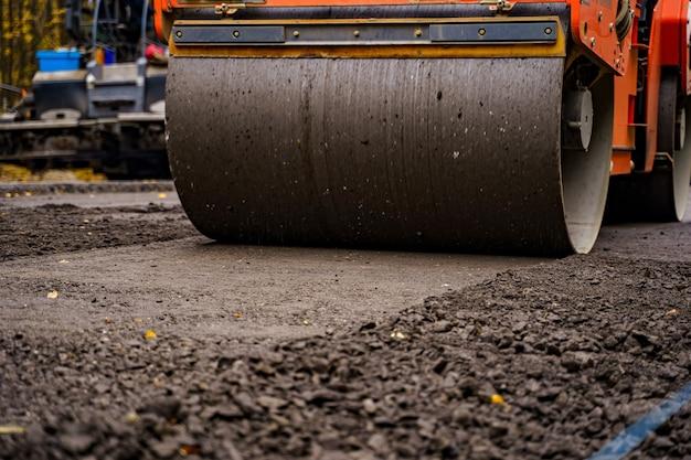 Straßenreparatur, verdichter legt asphalt. schwere spezialmaschinen. asphaltfertiger im einsatz. seitenansicht. nahaufnahme.