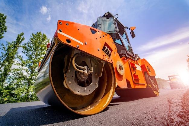 Straßenreparatur, verdichter legt asphalt. schwere spezialmaschinen. asphaltfertiger in betrieb. seitenansicht. nahansicht.