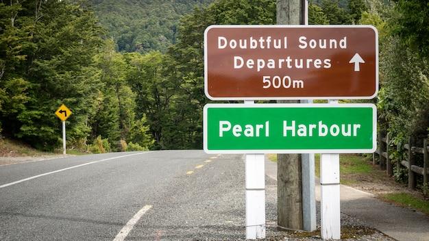 Straßenschild am straßenrand mit der aufschrift zweifelhafter ton und pearl harbor neuseeland