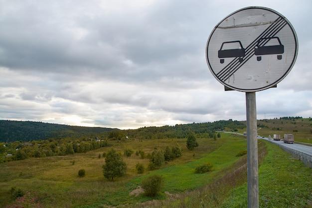 Straßenschild auf dem hintergrund der berge und des bewölkten himmels.