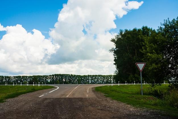 Straßenschild des nachgebens auf der kreuzung der unbefestigten straße vor der asphaltstraße. landschaft mit autobahn und bäumen. weiße wolken im blauen himmel. vorsichtiges fahren. verkehrsgesetze.
