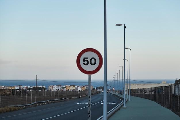 Straßenschild mit runder geschwindigkeitsbegrenzung über blauem himmel und meer