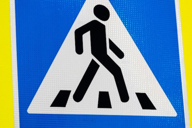 Straßenschildmann geht einen fußgängerüberweg entlang.