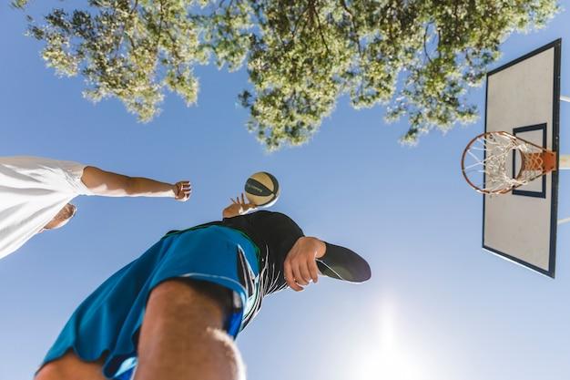 Straßenspieler zwei, der basketball gegen klaren himmel spielt