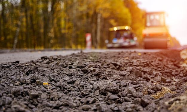 Straßenwalze, die neuen asphalt abflacht. schwere vibrationswalze bei der arbeit, die asphalt pflastert, straßenreparatur. selektiver fokus. unscharfer hintergrund.