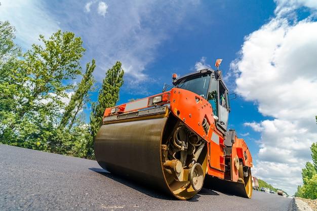 Straßenwalze, die neuen asphalt abflacht. schwere vibrationswalze bei der arbeit, die asphalt pflastert, straßenreparatur. selektiver fokus.