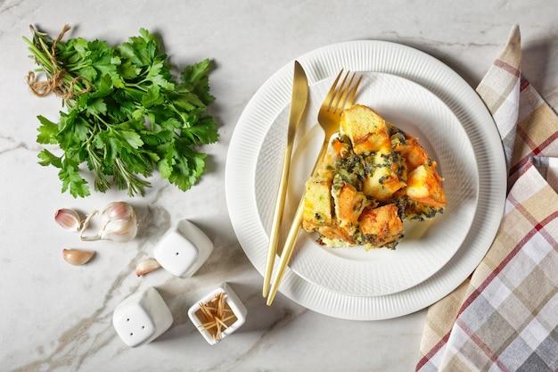 Strata oder italienischer frühstücksauflauf aus spinat, käse und eingeweichtem über nacht gewürfeltem brot mit senf auf einem weißen teller mit goldenem besteck auf weißem marmorhintergrund gebacken, nahaufnahme von oben