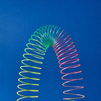 Stratching bunte spielzeugspirale in form der parabel auf einem blauen hintergrund mit kopienraum.