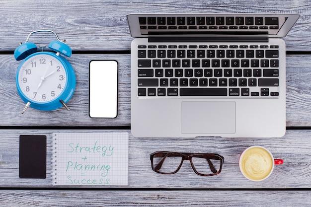 Strategie plus planung gleich erfolg. erfolgsformel. draufsicht-alarm-laptop-pc mit tasse kaffee und wecker auf einem weißen holztisch.