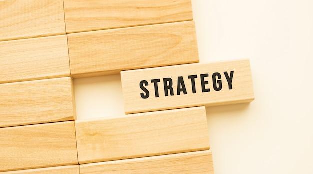 Strategie-text auf einem holzstreifen, der auf einem weißen tisch liegt
